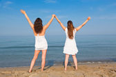 Two Young Women with Arms Outstretched on Seaside — Stock Photo