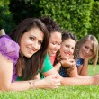 Teenage Female Friends Lying on Green at Park — Stock Photo #5851234