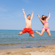 Happy Couple Jumping on the Beach at Seaside — Stock Photo #5908508