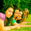 Teenage Female Friends Lying on Green at Park — Stock Photo #5908565