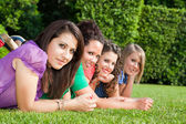 Teenage Female Friends Lying on Green at Park — Stock Photo