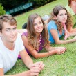 Group of Teenagers Lying on the Ground at Park - Stock Photo