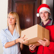 Delivery Boy with Christmas Hat and Box for Young Woman — Stock Photo