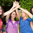 Teenage Female Friends with Hand in Stack - Stockfoto