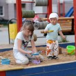 Siblings play in sandbox - Lizenzfreies Foto