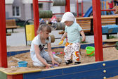 Siblings in sandbox — Stockfoto