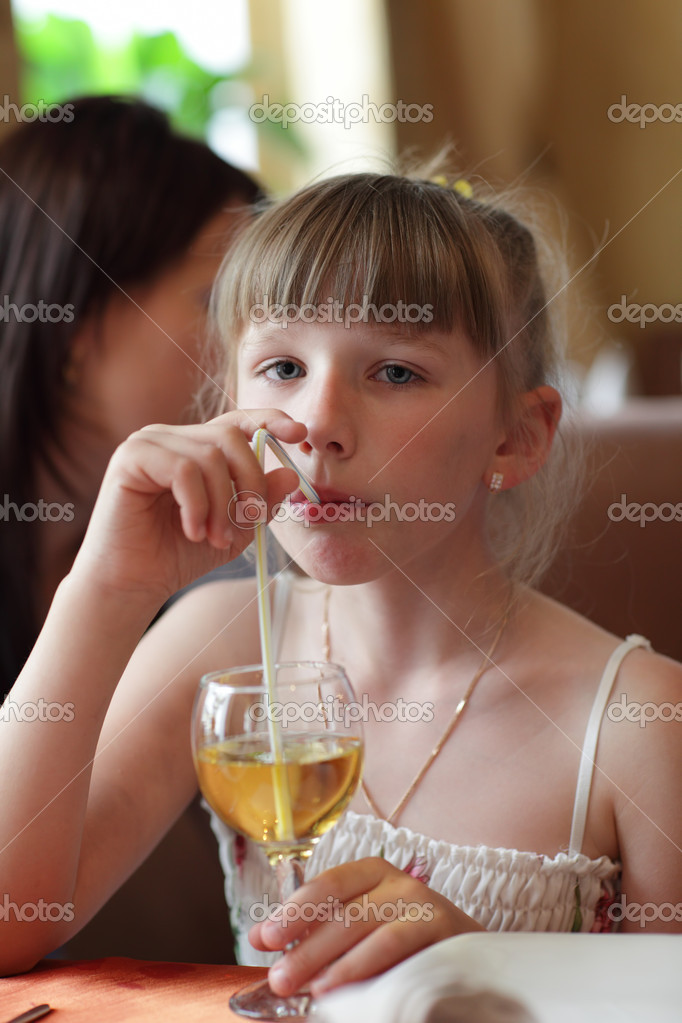 The girl drinks lemonade at the restaurant  Stock Photo #5906242