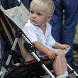 Sad boy in baby carriage - Stock Photo