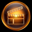 Stock Photo: Movie clapper board icon golden, isolated on black background.