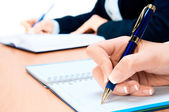 Cropped image of hand of young woman taking notes — Foto Stock