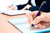 Imagem recortada da mão da jovem mulher tomando notas — Foto Stock