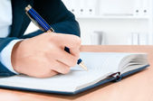 Cropped image of hand of young woman taking notes — Stock Photo