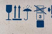 Packing symbols on old cardboard box — Stock Photo