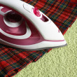 Electric iron and kilt — Stock Photo