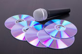 Vocal microphone and cd discs on table — Stock Photo