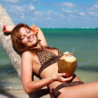 Woman in bikini on palm with coconut — Stock Photo #5890932