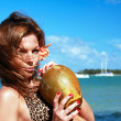 Woman in bikini resting on palm with coconut on beach — Stock Photo