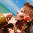 Woman drinking coconut water on caribbean beach — Stock Photo