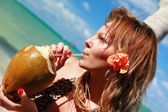 Woman drinking coconut water on caribbean beach — Stock Photo