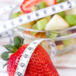 Fruit salad in white plate with measure tape — Stock Photo