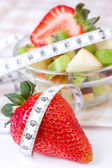Fruit salad in white plate with measure tape — Стоковое фото