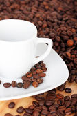 White cup with saucer on coffee beans — Stock Photo