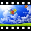 Filmstrip with color balloons in the dark blue sky — Stock Photo