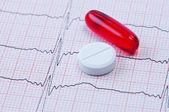 Capsule and tablet on cardiogram. — Zdjęcie stockowe
