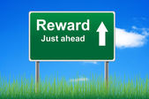 Reward road sign on sky background, grass underneath. — Stock Photo