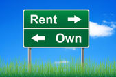 Rent and own road sign on sky background, grass underneath. — Stock Photo