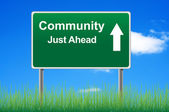Community road sign on sky background, grass underneath. — Stockfoto