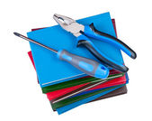 Building tool, screwdriver and pliers on a stack of books. — Stock Photo