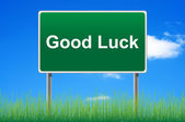 Good luck road sign on sky background. Bottom grass. — Stock Photo