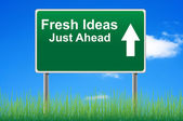 Fresh ideas road sign on sky background, grass underneath. — Stock Photo