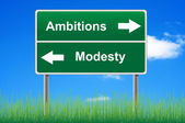 Ambitions modesty signpost on sky background, grass underneath. — Stock Photo