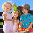 Cute blond little girl and boy in funny hat playing with fruits — Stock Photo #5382181
