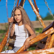 Serious little girl with blond long hair sitting on wooden chain — Stock Photo