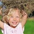 Cute little girl with blond curly hair playing with hay heap on - Stock Photo