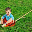 Little boy sitting on red plastic shovel over green grass lawn — Stock Photo