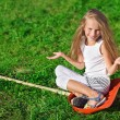Cute little girl with blond long hair sitting on red plastic sho — Stock Photo