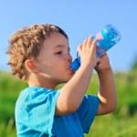 küçük çocuk yeşil çim sahada gaz su içme — Stok fotoğraf