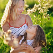 Beautiful mother and daughter family playing on meadow in sunset — Stock Photo