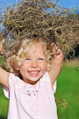 Cute little girl with blond curly hair playing with hay heap on — Stock Photo