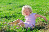Cute little girl with blond curly hair playing jn green lawn wit — Stock Photo