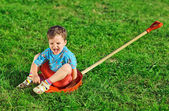 Little boy sitting on red plastic shovel over green grass lawn — ストック写真