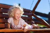 Cute little girl with blond curly hair playing on wooden chain s — Stock Photo