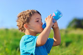 Little boy drinking gas water on green grass field — Stock Photo