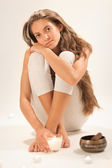 Sitting young beautiful woman SPA relaxing in studio on white — Stock Photo