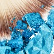 Makeup wide brush with blue crushed eye shadow - Stock Photo