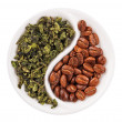 Green leaf tea versus coffee beans in Yin Yang shaped plate, iso — Stock Photo